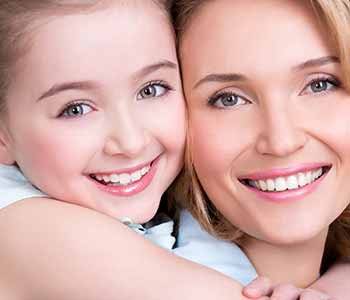Image of a mother & daughter smilling with showing their brighter teeth